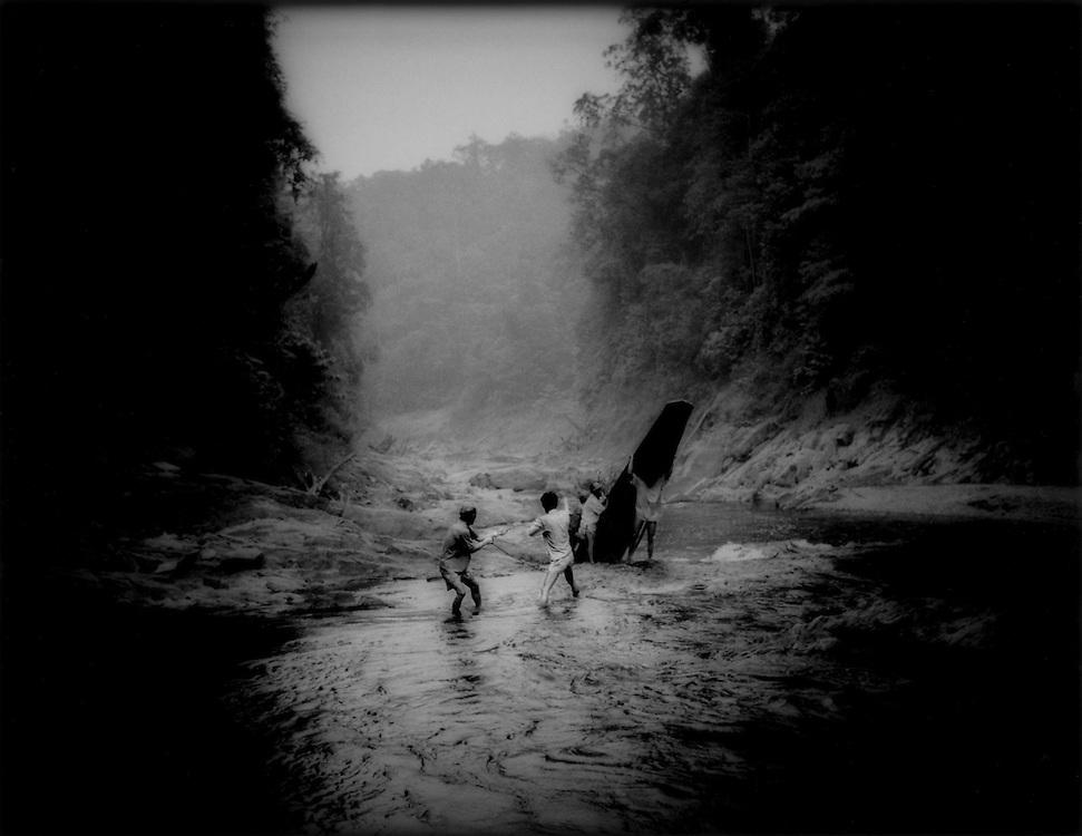 Iban Dayak men pull longboat over waterfall, Sungai Delok River, Sarawak, Malaysian Borneo.