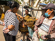 24 FEBRUARY 2015 - PHNOM PENH, CAMBODIA: Residents of the White Building buy dried fish from a street vendor in Phnom Penh. The White Building, the first modern apartment building in Phnom Penh, originally had 468 apartments, and was opened the early 1960s. The project was overseen by Vann Molyvann, the first Cambodian architect educated in France. The building was abandoned during the Khmer Rouge occupation. After the Khmer Rouge were expelled from Phnom Penh in 1979, artists and dancers moved into the White Building. Now about 2,500 people, mostly urban and working poor, live in the building. Ownership of the building is in dispute. No single entity owns the building, some units are owned by their occupants, others units are owned by companies who lease out apartments. Many of the original apartments have been subdivided since the building opened and serve as homes to two or three families. The building has not been renovated since the early 1970s and is in disrepair. Phnom Penh officials have tried to evict the tenants and demolish the building but residents refuse to move out.   PHOTO BY JACK KURTZ