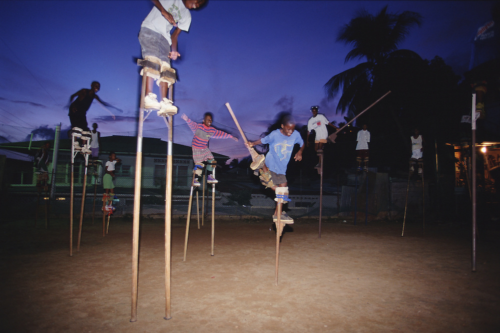 """Trinidad and Tobago """"MOKO JUMBIES: The Dancing Spirits of Trinidad"""".(During nighttime practice, Ekwon Jeffrey rehearses the one foot jump.).A photo essay about a stilt walking school in Cocorite, Trinidad..Dragon Glen de Souza founded the Keylemanjahro School of Art & Culture in 1986. The main purpose of the school is to keep children off the streets and away from drugs..He first taught dances like the Calypso, African dance and the jig with his former partner Cathy Ann Samuel.  Searching for other activities to engage the children in, he rediscovered the art of stilt-walking, a tradition known in West Africa as the Moko Jumbies , protectors of the villages and participants in religious ceremonies. The art was brought to Trinidad by the slave trade and soon forgotten..Today Dragon's school has over 100 members from age 4 and up..His 2 year old son Mutawakkil is probably the youngest Moko Jumbie ever. The stilts are made by Dragon and his students and can be as high as 12-15 feet. The children show their artistic talents mostly at the annual Carnival, which today is unthinkable without the presence of the Moko Jumbies. A band can have up to 80 children on stilts and they have won many of the prestigious prizes and trophies that are awarded by the National Carnival Commission. Designers like  Peter Minshall , Brian Mac Farlane and Laura Anderson Barbata create dazzling costumes for the school which are admired by thousands of  spectators. Besides stilt-walking the children learn the limbo dance, drumming, fire blowing and how to ride  unicycles..The school is situated in Cocorite, a suburb of Port of Spain, the capital of Trinidad and Tobago..all images © Stefan Falke"""