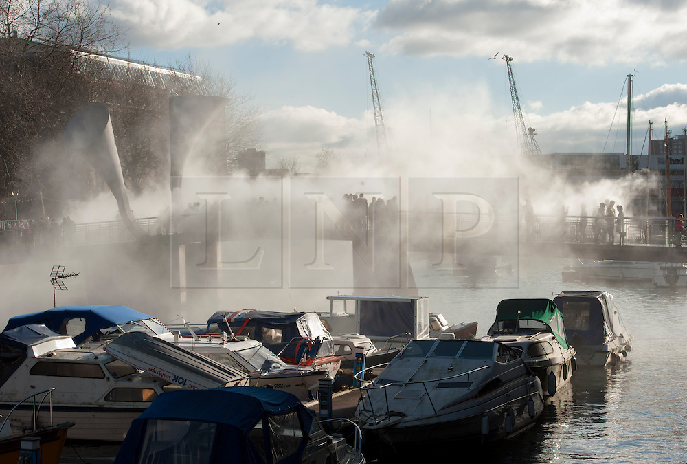 """© Licensed to London News Pictures.  14/02/2015. Bristol, UK.  Pero's bridge in Bristol docks disappears in a veil of fog as part of IBT/15 (In Between Time) arts festival.<br /> To celebrate Bristol's status as European Green Capital for 2015, IBT/15 invited a conjurer of unusual weather, artist Fujiko Nakaya to the city.  Over 40 years, Nakaya has used fog as a sculptural medium. Collaborating with the elements, Fujiko's clouds are created by water pumped at high pressure through many micro-fine nozzles.  """"The world is getting warmer – but how will this change our weather? And how might a changing climate disrupt our lives?""""  Pero's bridge is named after an African slave who lived in Bristol.  Photo credit : Simon Chapman/LNP"""