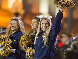 A WVU cheerleader waves to the crowd during a pep rally in downtown Memphis.