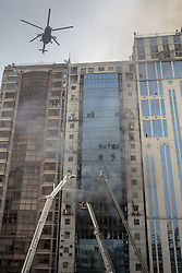 March 28, 2019 - Dhaka, Bangladesh - March 28, 2019 Dhaka, Bangladesh – Bangladeshi firefighters works on ladders to eclipse a blaze in Dhaka. A huge fire split through an office building at least 19 deaths in Dhaka, Bangladesh. (Credit Image: © KM Asad/ZUMA Wire)