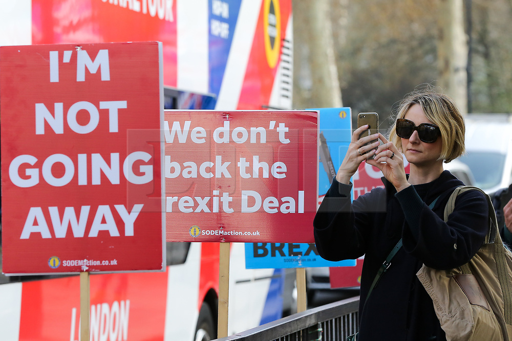 © Licensed to London News Pictures. 28/03/2019. London, UK. A woman takes a photograph of the placards by anti-Brexit demonstrators outside the Houses of Parliament. British Prime Minister Theresa May will seek a third vote on her Brexit deal on Friday 29 March 2019, subject to The Speaker, John Bercow's approval.  Photo credit: Dinendra Haria/LNP