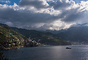 Morning sunlight breaks through clouds, illuminating the sea and mountains of the Amalfi Coast, Italy