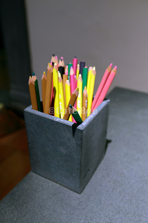 various pencils in basket on a table