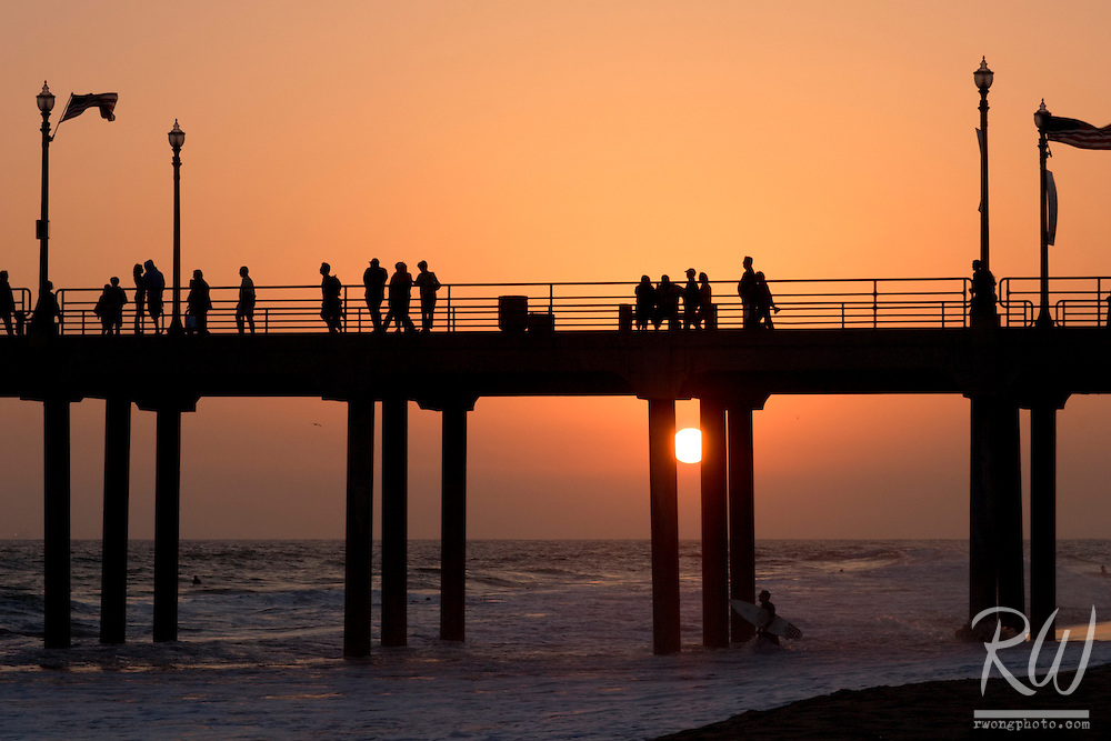 Surfer Under Huntington Beach Pier at Sunset, California