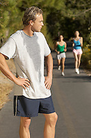 Male jogger pausing for breath on path