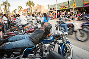 A biker rests on his Harley-Davidson as others ride past along Main Street during the 74th Annual Daytona Bike Week March 8, 2015 in Daytona Beach, Florida. More than 500,000 bikers and spectators gather for the week long event, the largest motorcycle rally in America.