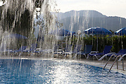 A view through the waterfall of an outdoor swimming pool.