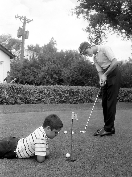 Practice putting with an audience. Golfer Tom Santori putts out with younger brother Sandy keeping close attention. 1963.