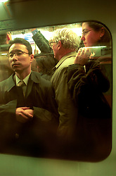 UK ENGLAND LONDON 13MAR02 - Commuters on overcrowded London underground trains. ..The London Underground is a rapid transit system serving a large part of Greater London and neighbouring areas of Essex, Hertfordshire and Buckinghamshire in the UK. The Underground has 270 stations and about 400 km of track, making it the longest metro system in the world by route length; it also has one of the highest number of stations and transports over three million passengers daily...jre/Photo by Jiri Rezac..© Jiri Rezac 2002