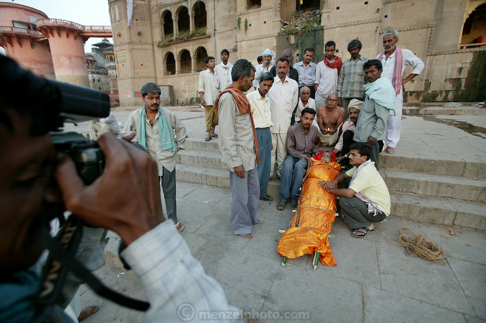 Gopal Jee Singh, 65, from Bihar, holds a butter lamp above his dead wife Subhadra Singh, 60 for a local photographer who takes photographs at the burning ghats and sells prints to families that want a keepsake. Subhadra died last night at 8 p.m. and he and his sons brought her here to Varanasi for the funeral rite, arriving at 3 a.m.