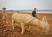LUOYANG, CHINA - MARCH 16: (CHINA OUT) <br /> <br /> A citizen passes by a stray cow at a construction site on March 16, 2016 in Luoyang, Henan Province of China. Various straw dolls like dinosaurs, ducks, Minions, elephants, pandas and small trains as well we others are made at a construction site which attracted citizens and visitors.<br /> ©Exclusivepix Media