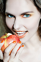 studio portrait of a beautiful woman holding apple fruit