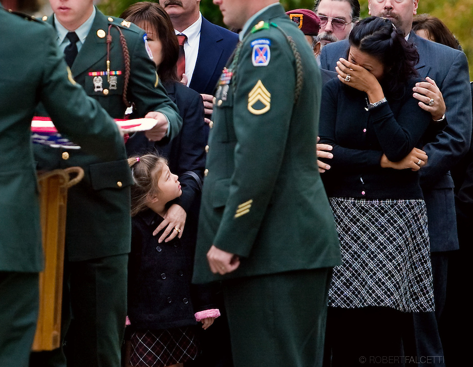 Katelyn Brennan, 4, looks up at her mother Kathy Brennan (r) as the casket of her father, U.S. Army Chief Warrant Officer William I. Brennan, is carried into the Church of the Nativity for funeral services October 25, 2004 in Bethlehem, Connecticut. Brennan, 36, an Army helicopter pilot, was killed in action in Baghdad, Iraq, October 16, 2004.   (Photo by Robert Falcetti)