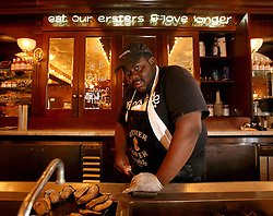 11june 2010. New Orleans, Louisiana. <br /> Oyster shucker Eric Bryant works in family owned renowned restaurant Arnaud's in the French Quarter. BP's disastrous environmental catastrophe out in the Gulf of Mexico threatens  the livelihood of many thousands of workers affiliated to the fishing industry in Louisiana. Thousands of barrels of oil per day continues to leak into the Gulf because of the explosion and collapse of the Deepwater Horizon drilling platform 46 miles out to sea. The closure of fishing grounds both east and west of the Mississippi river outflow is crippling thousands of local fishermen and all affiliated businesses and families who rely on the seafood industry.  <br /> Photo; Charlie Varley/varleypix.com