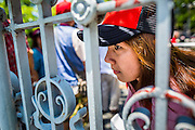08 MAY 2013 - BANGKOK, THAILAND: A member of the Red Shirts looks through the fence that surrounds the compound at the Thai parliament building during a Red Shirt protest. A splinter group of the Red Shirts, Thai supporters of exiled Prime Minister Thaksin Shinawatra, have besieged the Thai Constitutional Court for the last three weeks calling for the resignation of the justices, who have indicated they might oppose a proposed constitutional reform which would grant amnesty to people convicted of political crimes since 2007. This would probably include Thaksin. The justices have refused to step down. Wednesday the protesters moved their protest to the Thai Parliament, which is largely powerless to intervene.   PHOTO BY JACK KURTZ