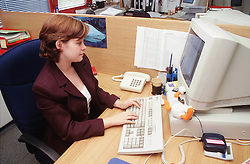 Young woman sitting at desk in office using computer,