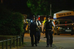 © Licensed to London News Pictures. 30/07/2020. London, UK. Police officers, forensics examiners and detectives at the scene of a fatal shooting that happened around 9pm on July 29th on Beaconsfield Road in Edmonton, North London where a man in his mid twenties was pronounced dead at the scene despite efforts of police and paramedics to save his life. Photo credit: Paul Davey/LNP