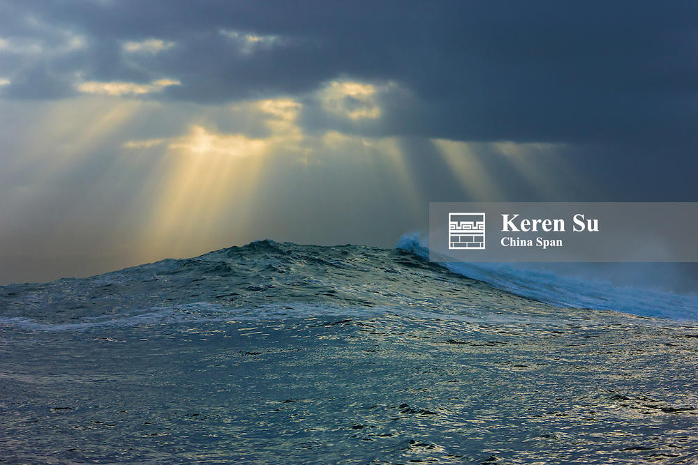 Sunlight breaking through the clouds above the ocean, False Bay, South Africa