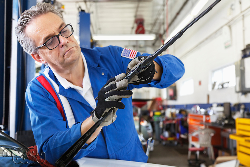Mechanic working on windshield wipers of car
