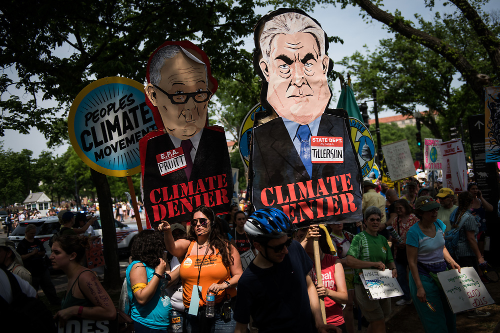 People carry signs protesting Secretary of State Rex Tillerson and Administrator of the EPA Scott Pruitt during the Climate March in Washington, D.C. on April 29, 2017. CREDIT: Mark Kauzlarich for CNN