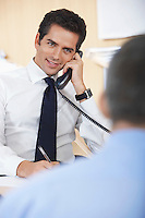 Businessman talking on phone in office silhouette of defocused man in foreground