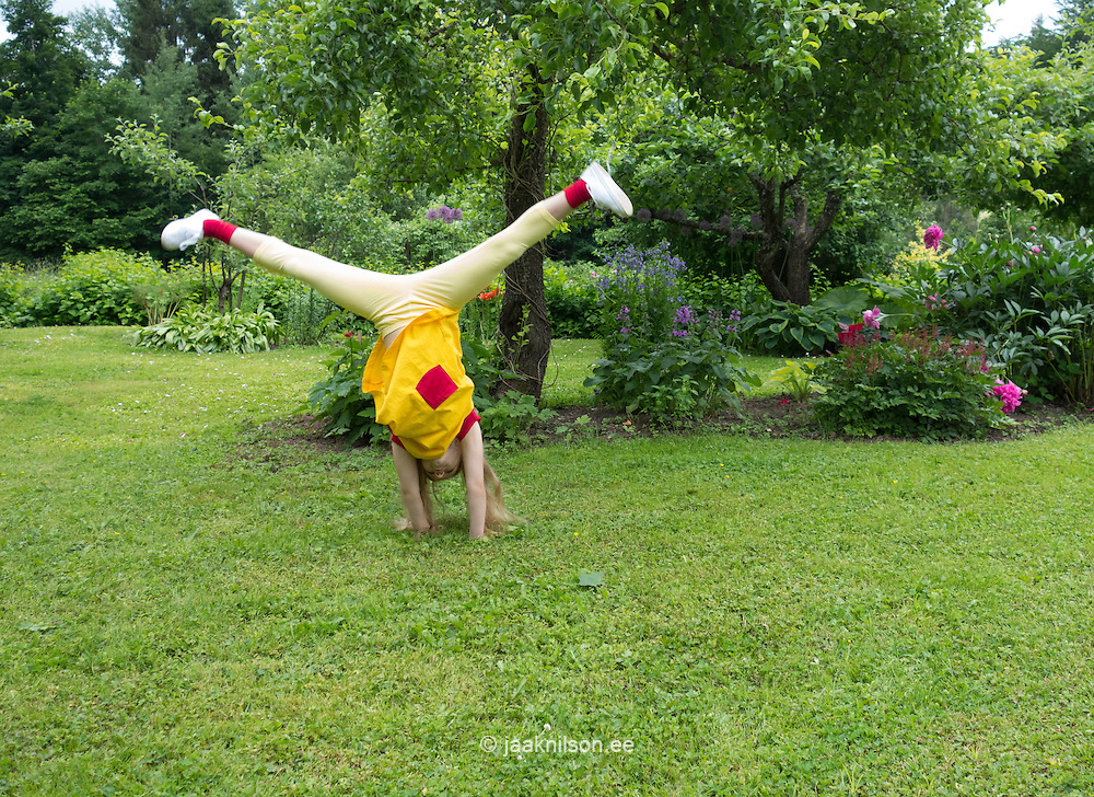 Kid turn to cartwheel in yard. Green, grass and flowerbed. Leisure activity, happy childhood. Estonia.