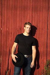 hot cowboy against a red barn