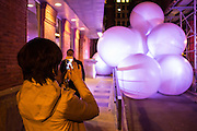 A bystander takes a photo of a pile of inflated balls on Jersey Street, part of an installation and performance by Snarkitecture in the Ideas City festival.