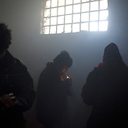 A group of young migrants socialise in one of the smoke filled warehouses in Belgrade.