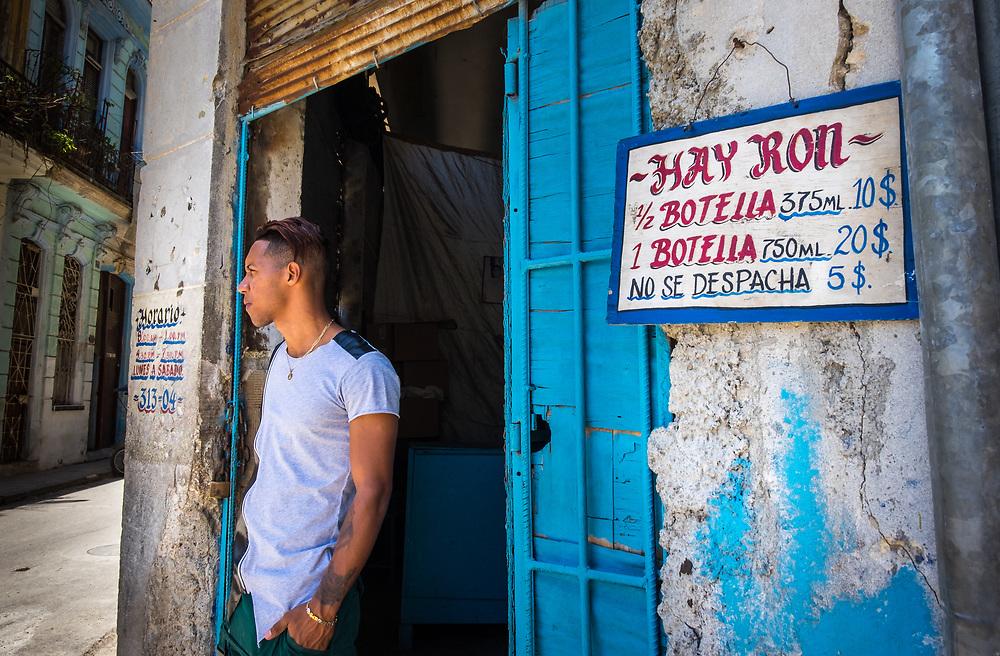 HAVANA, CUBA - CIRCA MAY 2016:  Man standing in front of shop selling rum to locals in Old Havana, Cuba.