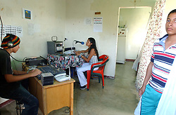 "Davis Semeco, left, plays music as Rosa Amarista, middle , hosts their radio show on ""A New Day Radio"", a community radio station in Caracas.  Sandino Pena, a community member stands in the foreground.  The station operates out of the home of Zulay Zerpa, who donates the space 7 days a week between 3pm and 9pm.  Chavez and his government have been increasingly supportive of these generally Chavista community media stations as a response to the anti-chavista private media."