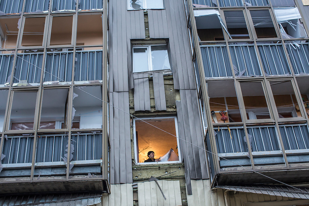 DONETSK, UKRAINE - FEBRUARY 2, 2015: A man fixes a window that was broken overnight when a shell landed just outside the apartment building in Donetsk, Ukraine. Ongoing fighting has killed scores of civilians since a tenuous ceasefire collapsed in late January. CREDIT: Brendan Hoffman for The New York Times