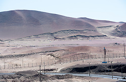 A shot of a part of the Peruvian desert with a road running through it.