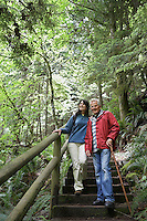 Senior man and middle-aged woman walking on forest trail