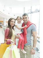 Father holding young girl posing with mother in shopping mall