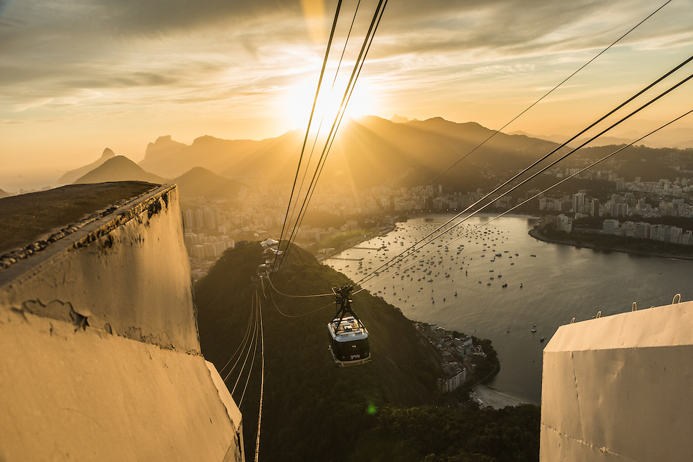Cablecar going up to the Sugarloaf mountain at sunset with on the background the statue of Christo redentor, Rio de Janeiro, Brazil.