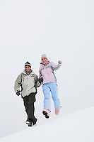 Couple running down snow-covered hill low angle view