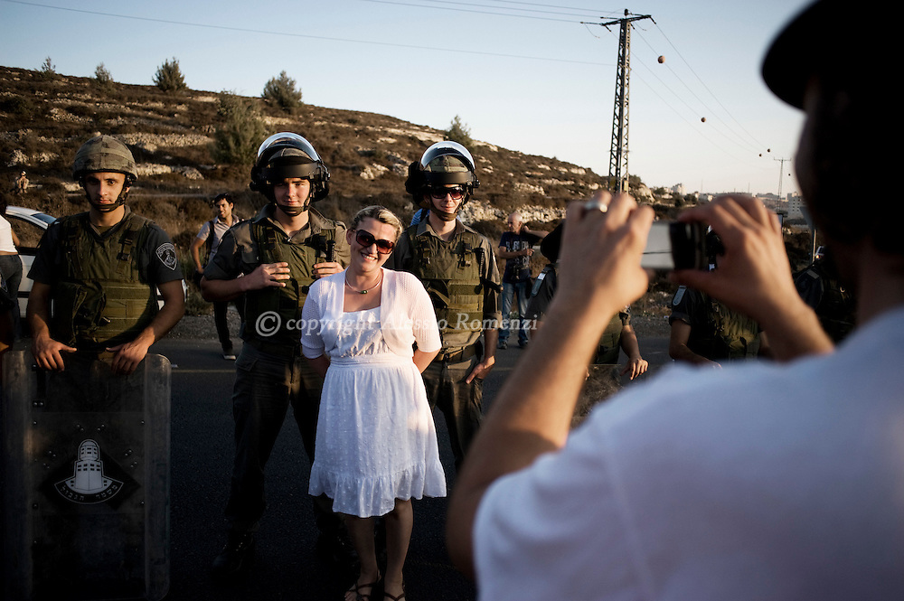 This picture shows a woman posing for a portrait among Israeli border policeman during the protest march against Palestinian bid for statehood at the United Nations on 20 September, 2011. ALESSIO ROMENZI