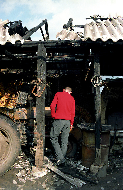 Marko examines his grandfather Zoran Kostic burned outhouse and tractor. The outhouse where Zoran, a farmer, kept his tractor and tools was burned the previous night, probably by Albanians. Preoce, Kosovo...Serbs living in enclaves in Kosovo.