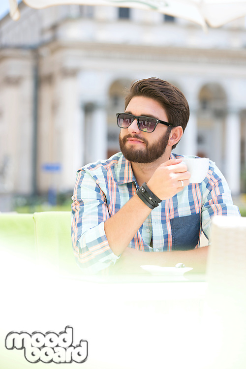 Mid-adult man looking away while having coffee at sidewalk cafe