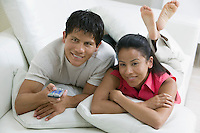 Couple lying on Couch with Remote Control front view