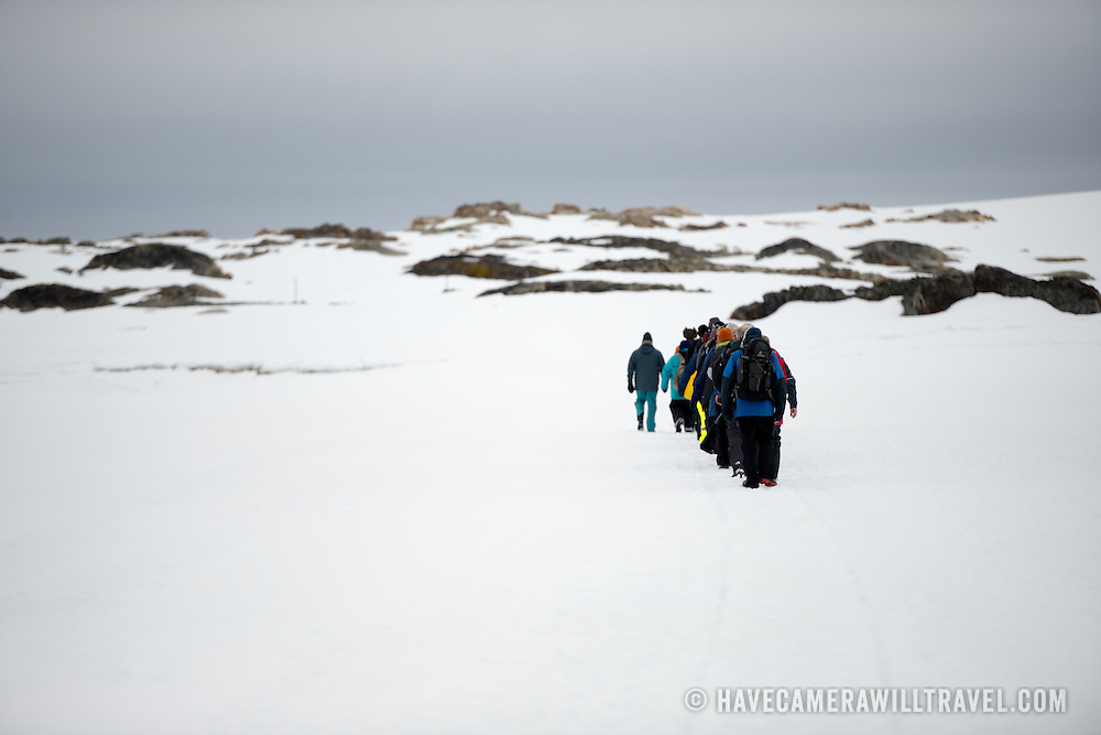 A line of tourists walk in single file across the sea ice towards Wordie House in Antarctica.