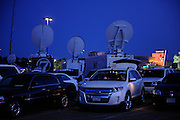 Aurora, CO- The theatre where a mass shooter killed and wounded many glows in background of many satellite news trucks at deep dusk on the day of the shooting.