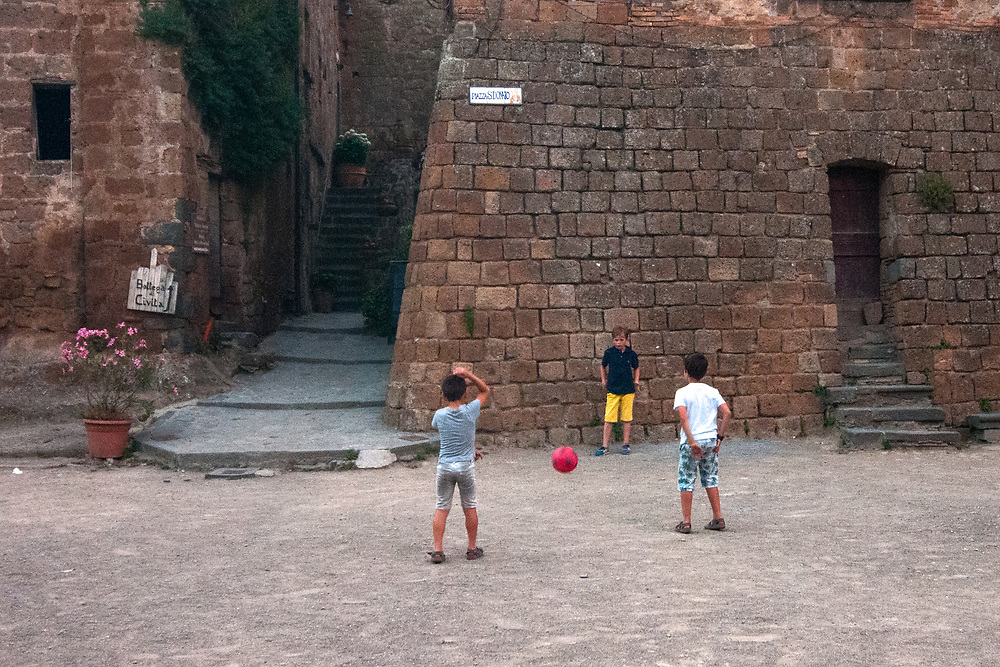 Children play in San Donato square in the village of Civita di Bagnoregio.<br /> Civita di Bagnoregio is a town in the Province of Viterbo in central Italy, a suburb of the comune of Bagnoregio, 1 kilometre (0.6 mi) east from it. It is about 120 kilometres (75 mi) north of Rome. Civita was founded by Etruscans more than 2,500 years ago. Bagnoregio continues as a small but prosperous town, while Civita became known in Italian as La citt&agrave; che muore (&quot;The Dying Town&quot;). Civita has only recently been experiencing a tourist revival. The population today varies from about 7 people in winter to more than 100 in summer.The town was placed on the World Monuments Fund's 2006 Watch List of the 100 Most Endangered Sites, because of threats it faces from erosion and unregulated tourism.