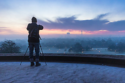 Primrose Hill, London, December 28th 2016. A cold, frosty and misty dawn greets London as seen from Primrose Hill, with the fog rolling in at around sunrise, obliterating the city's skyline and giving rise to soft, diffused tones. PICTURED: A photographer captures the wintery scene.