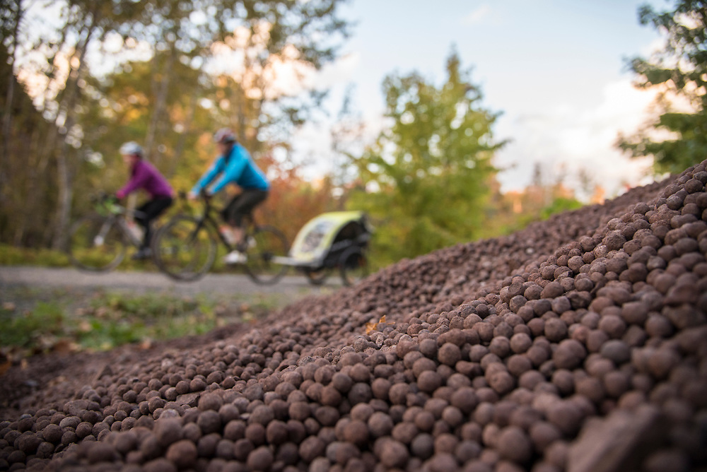 Iron Ore pellets line a section of the Iron Ore Heritage Trail where an active rail line passes over the trail while carrying ore pellets to shipping docks on Lake Superior nearby. The Iron Ore Heritage Trail is a multiuse recreation trail connecting communities in Marquette County on Michigan's Upper Peninsula.