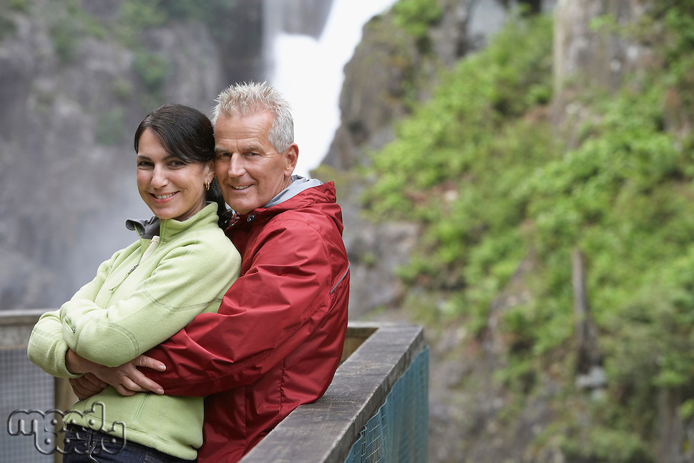 Portrait of couple posing by railing in mountains