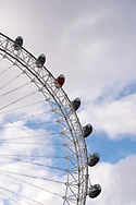 Low angle view of one orange and six white passenger capsules of the London Eye, also known as the Millennium Wheel, against the sky in London, England.